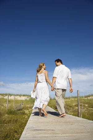 bald head island: Caucasian mid-adult couple holding hands walking down beach access path.