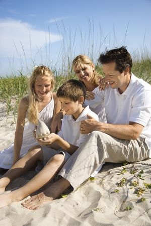 Caucasian family of four sitting on beach looking at seashell. Stock Photo