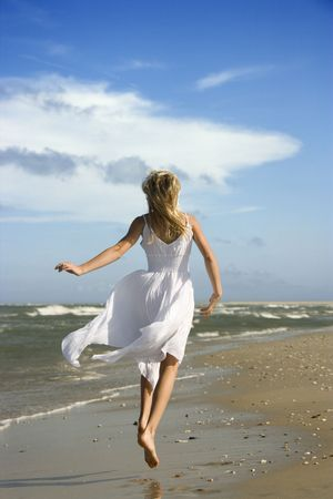 frolic: Caucasian pre-teen girl running down the beach in flowing white dress.