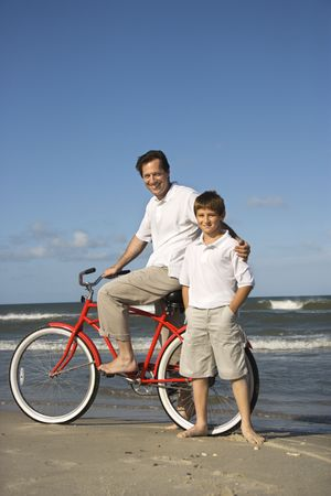 beach cruiser: Caucasian father and pre-teen boy standing on beach with bicycle.
