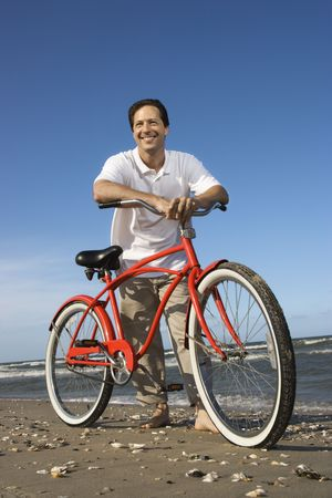 beach cruiser: Caucasian mid-adult man posing with red bicycle on beach.