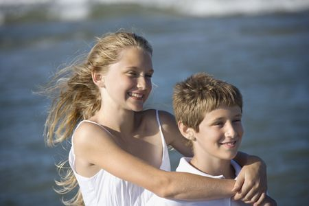 bald girl: Caucasian pre-teen girl with arms around pre-teen boy on beach. Stock Photo