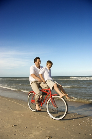 beach cruiser: Caucasian father on bicycle with pre-teen boy riding on handlebars. Stock Photo