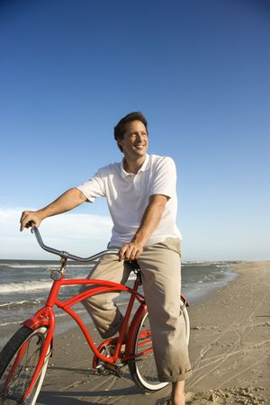 Caucasian mid-adult man posing on bicycle on beach. photo