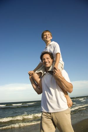 Caucasian father with pre-teen boy on shoulders on beach. Stock Photo