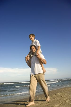 Caucasian father with pre-teen boy on shoulders on beach. photo