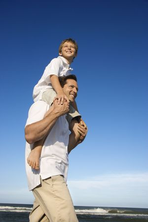 Caucasian father with pre-teen on shoulders on beach. photo