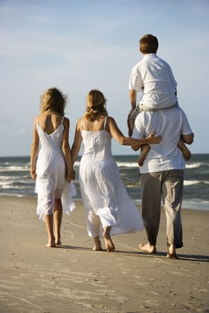 Caucasian family of four walking on beach with dad carrying son on shoulders. photo