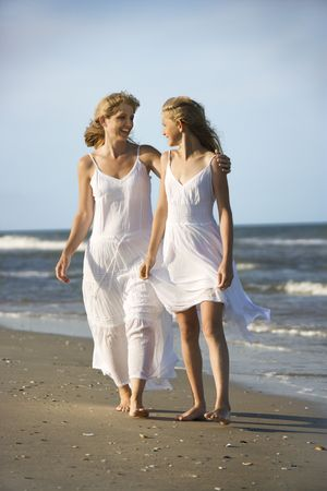 Caucasian mother and pre-teen girl walking on beach holding hands. photo