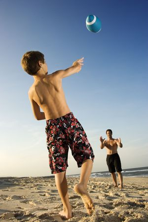 Caucasian pre-teen boy throwing football to mid-adult male. photo