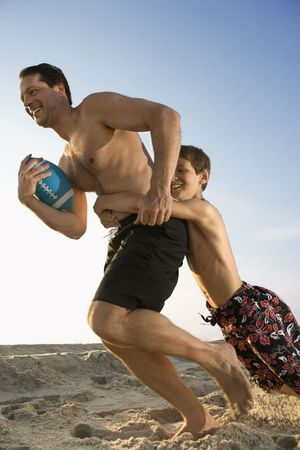 Caucasian mid-adult man running with football being tackled by pre-teen boy. photo
