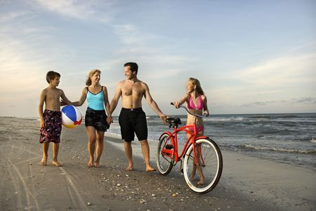 bicycle walk: Caucasian family of four walking on beach.