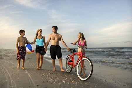 Caucasian family of four walking on beach. Stock Photo - 1762066
