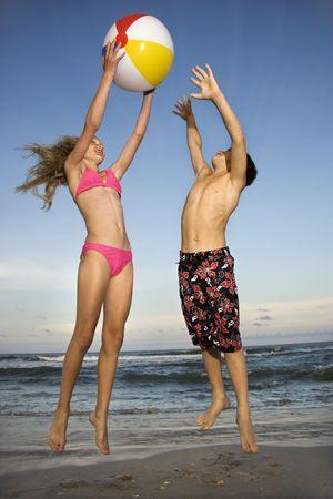 enfant maillot: Du Caucase pr�-adolescents fille et gar�on jouant avec beachball sur la plage.