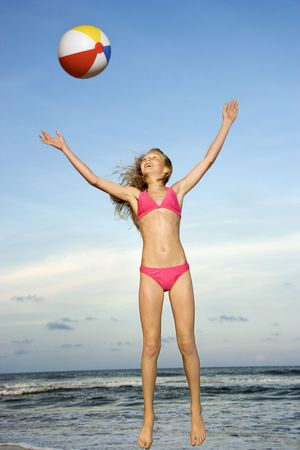 Caucasian pre-teen girl playing with beachball on beach.