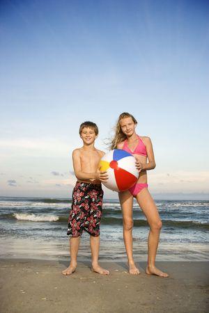 beachball: Caucasian pre-teen boy and girl holding beachball on beach.