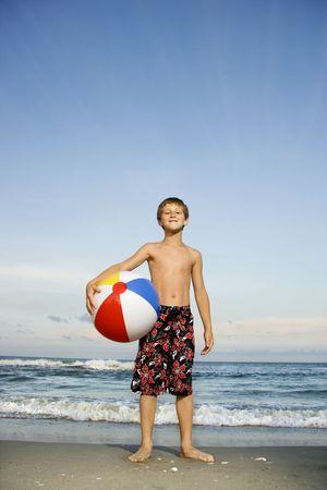 beachball: Caucasian pre-teen boy holding beachball on beach.