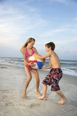 brother sister fight: Caucasian pre-teen boy and girl pulling on beachball. Stock Photo