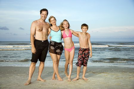 bald girl: Caucasian family of four standing on beach.