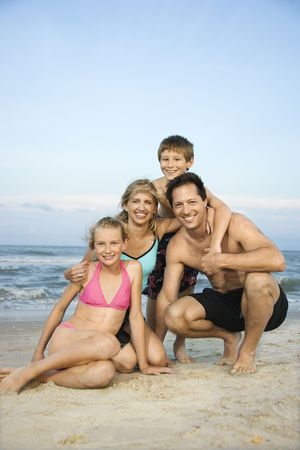 preteen girl: Caucasian family of four posing together on beach.