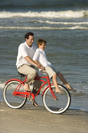 Father riding bicycle on beach with pre-teen son on handlebars. photo