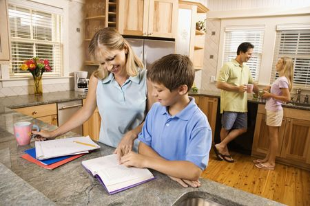 two people with others: Caucasian family in kitchen doing homework and chatting.