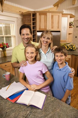 supervise: Caucasian family of four standing in kitchen posing with homework on counter.