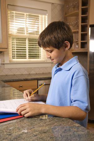 preteen boy: Caucasien pr�-ado gar�on � faire des devoirs � la cuisine.