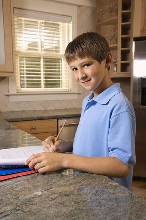 preteen boy: Du Caucase pr�-adolescent gar�on � faire des devoirs � la recherche de cuisine au spectateur et souriant.
