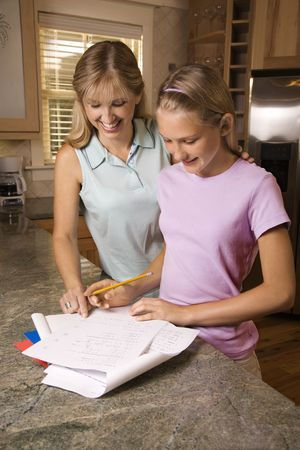 supervise: Caucasian mid-adult mother helping pre-teen daughter with homework at kitchen counter.