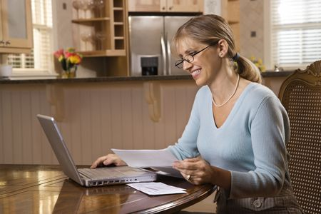 Caucasian mid-adult woman paying bills on laptop computer.