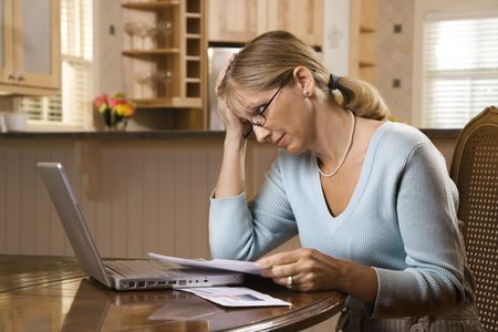 Caucasian mid-adult woman paying bills on laptop computer resting head in hand with worry. photo
