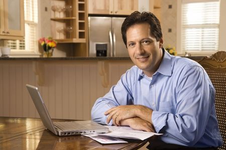 Caucasian mid-adult man paying bills on laptop computer looking at viewer and smiling.