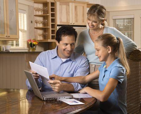 Caucásicos familia en el pago de facturas de ordenador portátil.