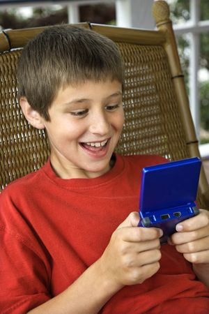 preteen boy: Caucasian pre-teen boy playing handheld video game and smiling.