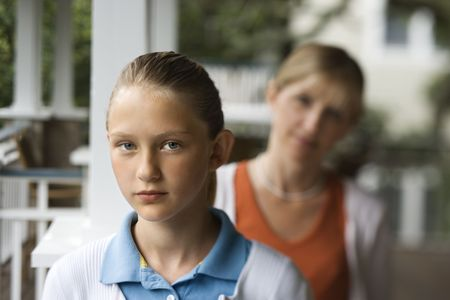 looking over shoulder: Caucasian pre-teen girl with mother behind her looking over shoulder. Stock Photo