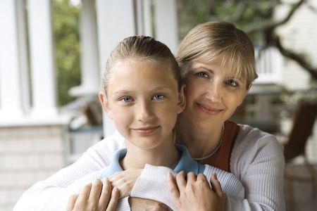 Caucasian mid-adult mother hugging pre-teen daughter.