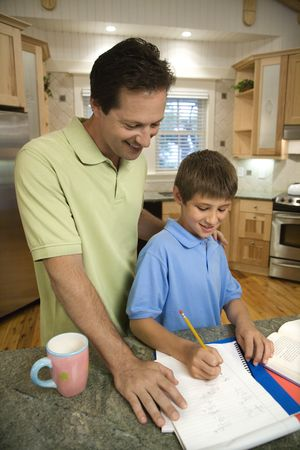 supervise: Caucasian mid-adult father helping pre-teen son with homework in kitchen.