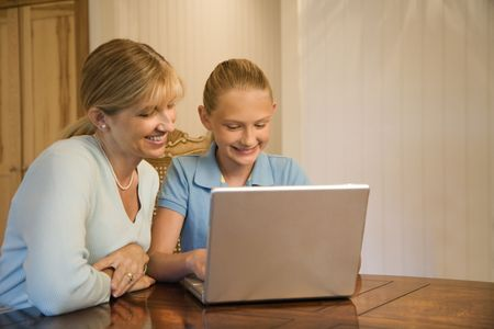 Caucasian mid-adult woman and pre-teen  girl using laptop computer. photo