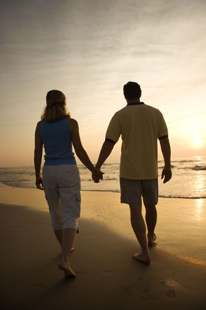 love image: Caucasian mid-adult couple walking holding hands on beach at sunset.