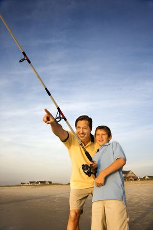 Caucasian mid-adult man shore fishing on beach with pre-teen boy and pointing. Stock Photo