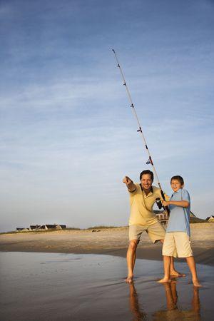 preteen boy: P�che caucasienne de rivage dhomme dmi-adulte sur la plage avec le gar�on de la pr�adolescence et le pointage. Banque d'images