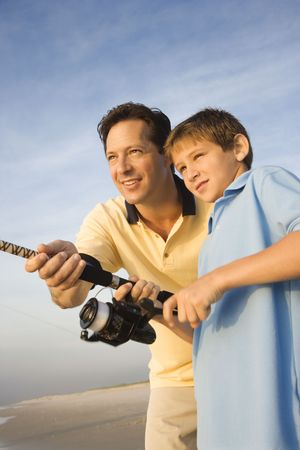 Caucasian mid-adult man shore fishing on beach with pre-teen boy photo