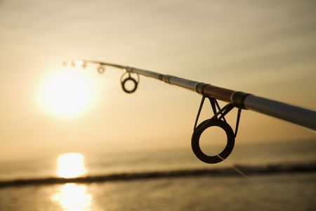 fishing pole: Fishing pole against ocean at sunset.