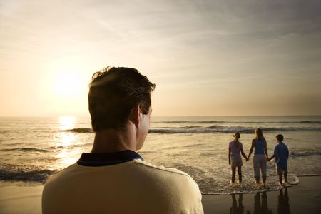 appreciating: Caucasian mid-adult man standing and watching mid-adult woman with children on beach.