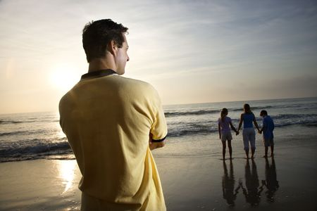one person with others: Man standing and watching mid-adult woman with children on beach. Stock Photo