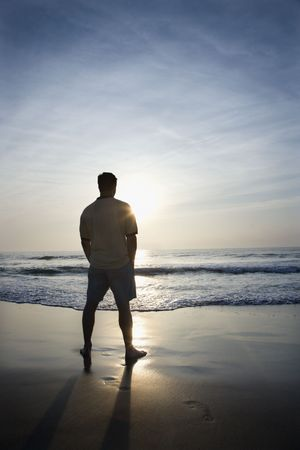Prime adult man standing alone on beach looking at ocean at sunrise.