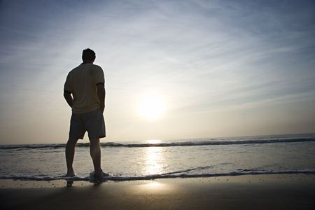 standing alone: Prime adult man standing alone on beach looking at ocean at sunrise.