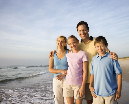 Portrait of Caucasian family of four posing on beach looking at viewer smiling. photo
