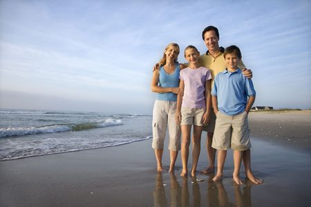 color photographs: Portrait of Caucasian family of four posing on beach looking at viewer smiling.